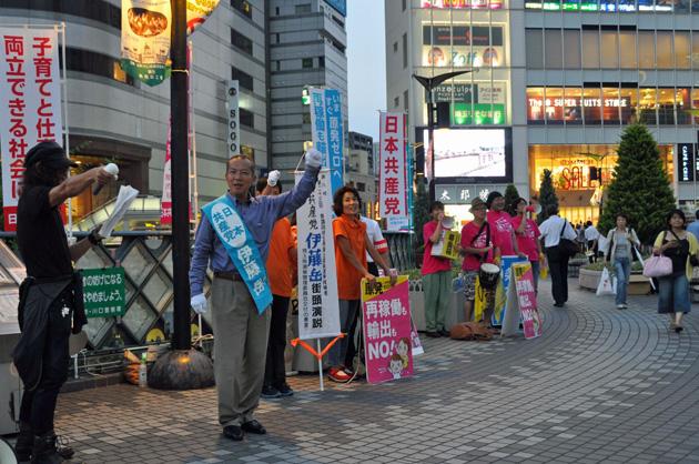 川口駅西口デッキ上で、「怒りのドラム隊」の村上ダミアン勝さんの応援も受け、市民に訴える伊藤岳候補=18日