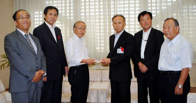 土橋義男副市長(右から3人目)に募金を渡す黒崎本部長(左から3人目)、村岡県議(同2人目)ら=2013年10月10日、行田市