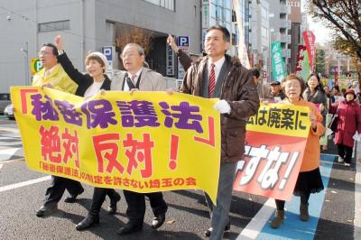 「秘密保護法絶対反対」と訴えてデモ行進する人たち=2013年12月4日、さいたま市
