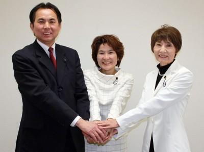 柳下(右)、村岡(左)両県議とがっちり握手する奥田氏(中央)=2014年3月3日、県議会