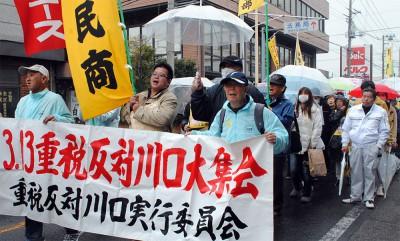 雨の中「消費税増税反対」と訴えて歩く人たち=2014年3月13日、川口市
