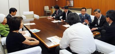 市の担当者(手前)に党のアピールを紹介する山崎市議団長(右側手前)ら=2014年5月16日、さいたま市役所
