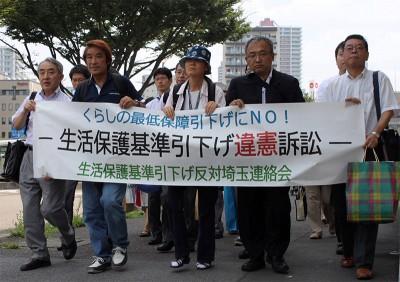 「生活保護基準引き下げは憲法違反」を裁判所までデモ行進する原告と弁護団=2014年8月1日、さいたま市