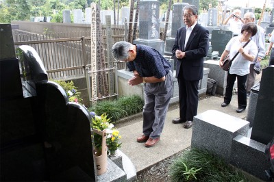さんの墓前で手を合わせる参加者=2014年9月4日、さいたま市