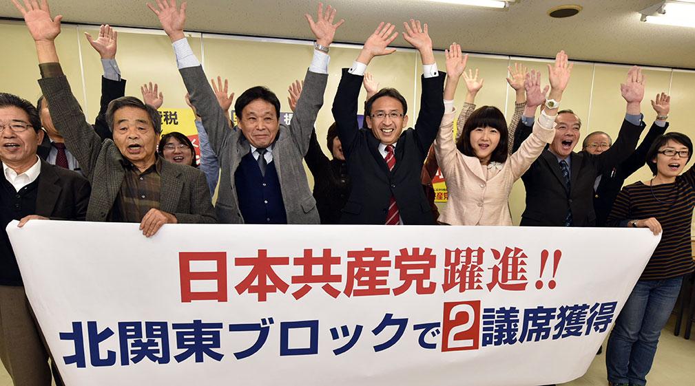 衆院北関東ブロックで2議席を獲得し、喜びの万歳をする(左4人目から)塩川鉄也、梅村早江子両氏ら=2014年12月14日夜、さいたま市