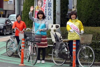 おかざき候補(右端)と自転車で町中を宣伝する梅村衆院議員(その隣)=2015年3月21日、戸田市