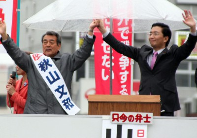 聴衆の声援にこたえる(左から)秋山文和県議候補と山下芳生書記局長=2015年4月5日、春日部市