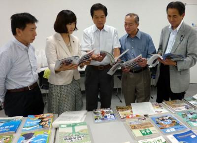 教科書を閲覧する(右から)村岡県議、伊藤氏、(一人おいて)梅村衆院議員=2015年6月30日、さいたま市