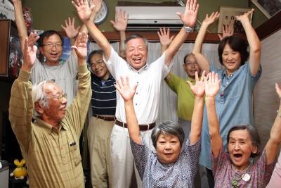 当選を喜ぶ神辺氏(中央)=2015年7月12日、越生町